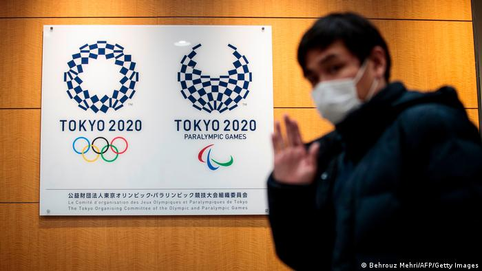 A reporter gestures as he walks past the logos of Tokyo 2020 Olympic Games