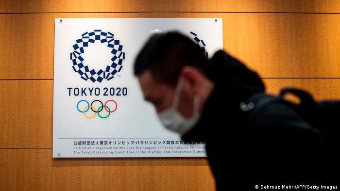 Логотип Олимпиады в Токио на плакате и человек в маске