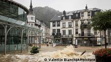 A shopkeeper watches floodwaters run down a main street in the center of Spa, Belgium, Wednesday, July 14, 2021. A code red was issued in parts of Belgium on Wednesday as severe rains hit the area. (AP Photo/Valentin Bianchi)