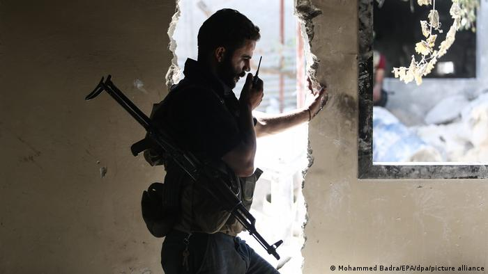 A Jaish al-Islam fighter communicates through a radio with other fighters at Tal al-Siwan area in the rebel-held town of Douma