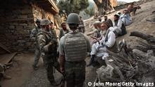 KORENGAL VALLEY, AFGHANISTAN - OCTOBER 25: Village elders speak with a U.S. Marine (L), through an interpreter as Afghan forces search for weapons October 25, 2008 in the Korengal Valley of Kunar Province in eastern Afghanistan. Taliban insurgents enjoy widespread public support in the contested valley, site of some of the heaviest fighting between U.S. forces and the Taliban. (Photo by John Moore/Getty Images)