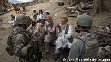 Afghan villagers speak with a US marine (L) as Afghan forces search for weapons in 2008 in Kunar province