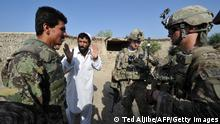 An Afghan soldier (L) serves an interpreter as a civilian talks to US soldiers from Viper Company (Bravo), 1-26 Infantry during a patrol at a village near Combat Outpost (COP) Sabari in Khost province in eastern Afghanistan June 19, 2011. Defense Secretary Robert Gates confirmed June 19, that US officials were involved in preliminary talks with the Taliban to seek a political solution to the Afghan war but said he didn't expect significant progress for months. AFP PHOTO/TED ALJIBE (Photo credit should read TED ALJIBE/AFP via Getty Images)