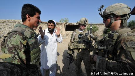 Afghan soldier, on the left, serves an interpreter as a civilian talks to US soldiers