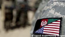 An Afghan interpreter working with the 101st Airborne Division Alpha Battery 1-320th displays a patch showing the Afghan and US flags at Combat Outpost Nolen on the outskirts of Arghandab valley's Jellawar town on September 9, 2010. The United States and NATO have 150,000 troops in Afghanistan aiming to quell the insurgency that began soon after the Taliban regime was overthrown in a US-led invasion in late 2001. AFP PHOTO/PATRICK BAZ (Photo credit should read PATRICK BAZ/AFP via Getty Images)