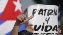 Ein kubanischer Demonstrant hält ein Schild hoch mit der Aufschrift Freiheit und Leben