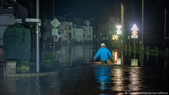 A fireman wades through a street flooded by the Kyll River in Kordel, Rheinland-Pfalz