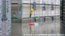 Ein Mann steht auf einem Gerüst und betrachtet die überflutete Straße vor dem Haus. +++ dpa-Bildfunk +++