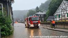 14.07.2021 Solingen Wasser steht in einer Straße in Solingen Unterburg. Der Eschbach (r) ist über die Ufer getreten.