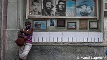 An elderly woman stands next to pictures of Cuban late leaders in a street of Havana, on July 14, 2021. - One person has died in the anti-government protests across Cuba, according to officials, with activists saying at least 100 people have been arrested and scores remain in detention as demonstrations overseas in solidarity continued. (Photo by YAMIL LAGE / AFP)