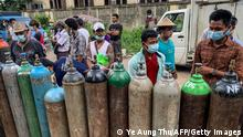 This picture taken on July 14, 2021 shows people waiting to fill up empty oxygen canisters outside a factory in Yangon, amid a surge in the number of Covid-19 coronavirus cases. - Residents across Myanmar's biggest city are defying a military curfew in a desperate search for oxygen to keep their loved ones breathing as a new coronavirus wave crashes over the coup-wracked country. - TO GO WITH Myanmar-health-virus-oxygen, FOCUS (Photo by Ye Aung THU / AFP) / TO GO WITH Myanmar-health-virus-oxygen, FOCUS (Photo by YE AUNG THU/AFP via Getty Images)