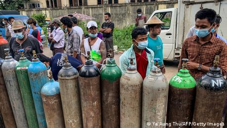 People wait to fill up empty oxygen cylinders outside a factory in Yangon, amid a surge in COVID cases