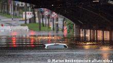 Köln, nur das Dach eines Autos schaut noch aus dem Wasser, das eine Bahnunterführung geflutet hat.