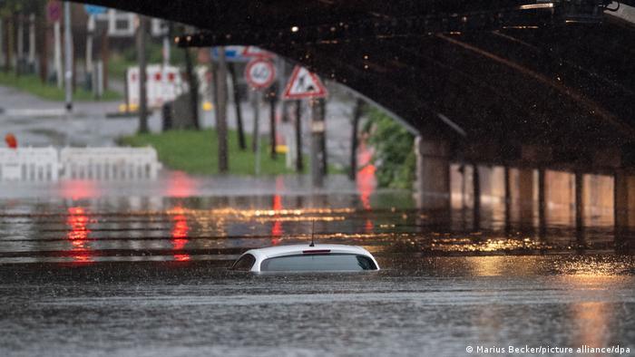 Tempestades e enchentes na Alemanha: topo de carro se projeta da água em passagem subterrânea de ferrovia inundada.