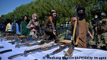 Taliban fighters put down their weapons as they surrendered to join the Afghanistan government during a ceremony in Herat on 24, 2021. (Photo by HOSHANG HASHIMI / AFP) (Photo by HOSHANG HASHIMI/AFP via Getty Images)