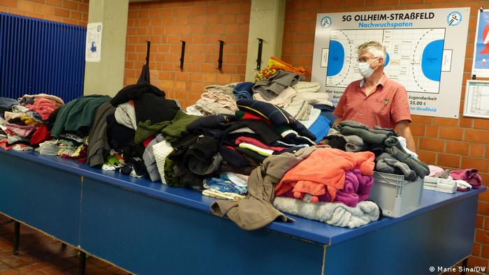 A volunteer stands behind a table heaped with donated clothes