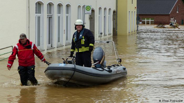 Firefighters and a motorboat in flooded road