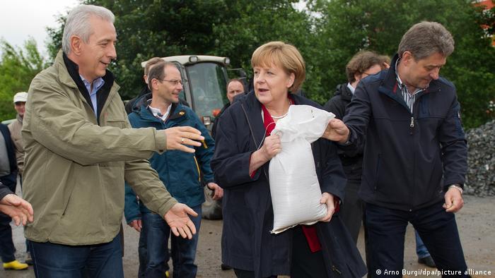 2013 in Pirna: Angela Merkel reicht dem damaligen sächsischen Ministerpräsidenten, Stanislav Tillich, einen Sandsack