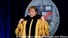 German Chancellor Angela Merkel is awarded with a Doctor of Humane Letters, honoris causa, by John Hopkins University President Ronald Daniels at the Johns Hopkins School of Advanced International Studies campus in Washington, Thursday, July 15, 2021. (AP Photo/Manuel Balce Ceneta)