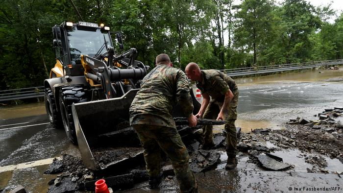 Two Bundeswehr soldiers throwing a large piece of asphalt into the the bucket of a loader on a road in Hagen, Germany