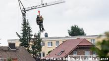 Mit einer Seilwinde werden ein Besatzungsmitglied und ein Mann in einen Rettungshubschrauber der Bundeswehr gezogen.