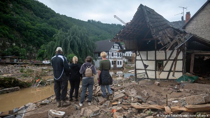 People stand near a collapsed older home in Ahrweiler