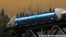 "*** Dieses Bild ist fertig zugeschnitten als Social Media Snack (für Facebook, Twitter, Instagram) im Tableau zu finden: Fach ""Images"" —> Weltspiegel/Bilder des Tages *** Firefighters spray water from a fire train to hot spots along the tracks over Rock Creek Bridge as the Dixie Fire grows in Plumas National Forest, California, U.S., July 15, 2021. REUTERS/David Swanson TPX IMAGES OF THE DAY"