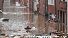 """*** Dieses Bild ist fertig zugeschnitten als Social Media Snack (für Facebook, Twitter, Instagram) im Tableau zu finden: Fach """"Images"""" —> Weltspiegel/Bilder des Tages *** TOPSHOT - A woman is trying to move in a flooded street following heavy rains in Liege, on July 15, 2021. Illustration shows the scene in Liege after heavy rainfall, Thursday 15 July 2021. - The provincial disaster plan has been declared in Liege, Luxembourg and Namur provinces after large amounts of rainfall. Water in several rivers has reached alarming levels. - Belgium OUT (Photo by BRUNO FAHY / Belga / AFP) / Belgium OUT (Photo by BRUNO FAHY/Belga/AFP via Getty Images)"""
