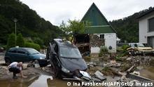 """*** Dieses Bild ist fertig zugeschnitten als Social Media Snack (für Facebook, Twitter, Instagram) im Tableau zu finden: Fach """"Images"""" —> Weltspiegel/Bilder des Tages *** TOPSHOT - A resident kneels next to damaged cars and houses after heavy rain and floods in Hagen, western Germany, on July 15, 2021. - Heavy rains and floods lashing western Europe have killed at least 42 people in Germany and left many more missing, as rising waters led several houses to collapse. (Photo by INA FASSBENDER / AFP) (Photo by INA FASSBENDER/AFP via Getty Images)"""