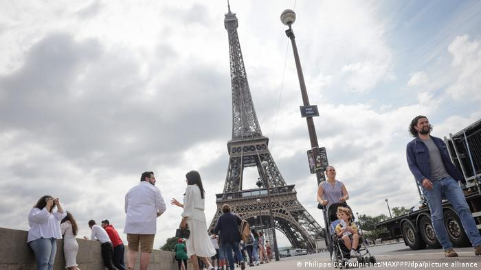Visitors stroll past the Eiffel Tower ahead of its reopening