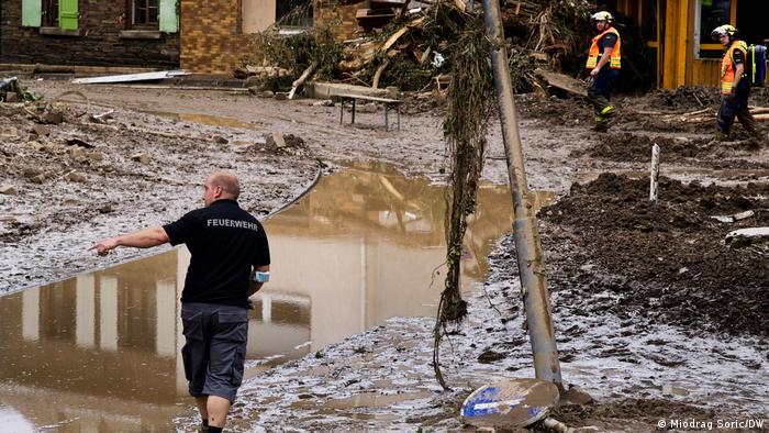 Three firemen surveying a flood-damaged street in Walporzheim, Germany