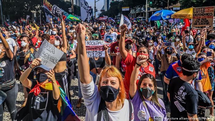 Foto mostra muitas pessoas protestando. Elas usam máscara. Algumas erquem o punho e outras, cartazes.