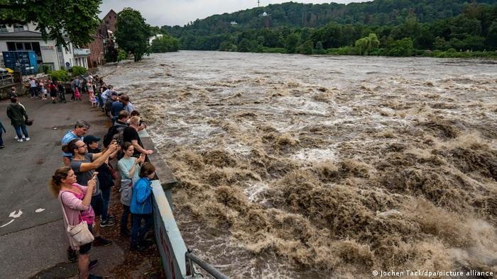 A group of people taking photos of raging waters at the flooding Baldeney Lake Dam in Essen, Germany
