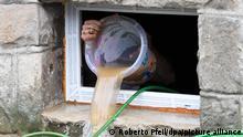 15/07/2021*** Ein Anwohner beseitigt seine Schäden im Keller, in dem er kurzerhand das Wasser mit einem Eimer aus dem Keller befördert, die die Überflutung der Nahmer gestern abend mit sich gebracht hat. Durch die heftigen Regenfälle war das Flüsschen zum reissenden Fluss geworden.