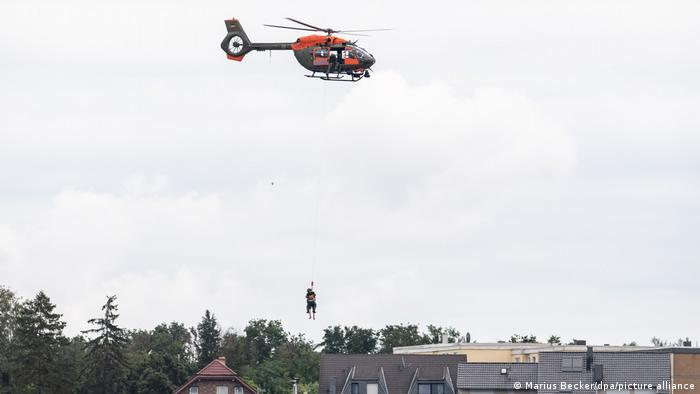 A helicopter team rescuing a person from a flooded building