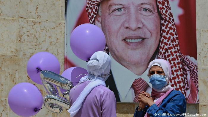 Dua perempuan melintas di depan poster Raja Abdullah II dari Yordania