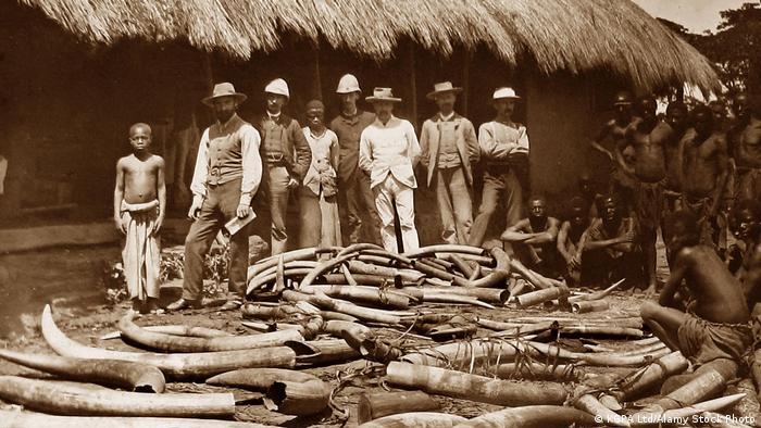 Weiße Kolonialherren stehen vor einem Berg von Elefanten-Stoßzähnen, beäugt von hockenden Schwarzafrikanern.