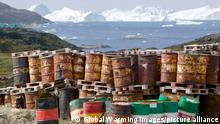 waste oil barrels on the tundra outside Illulissat in Greenland with icebergs behind from the Sermeq Kujullaq or Illulissat Ice fjord. The Illulissat ice fjord is a Unesco world heritage site