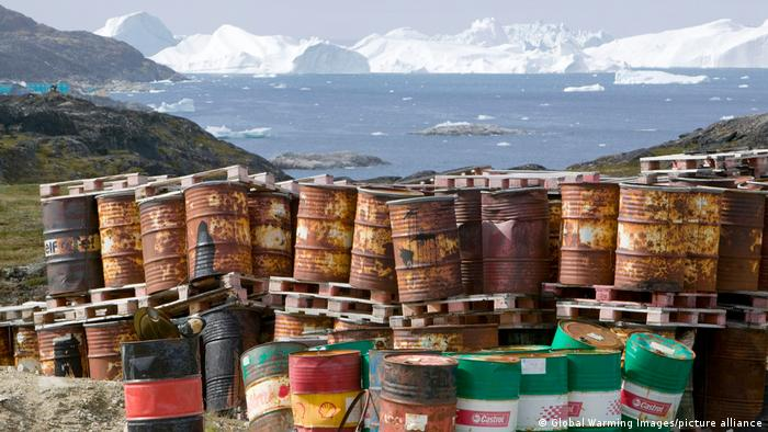 Waste oil barrels on the tundra outside Illulissat in Greenland with icebergs behind from the Sermeq Kujullaq or Illulissat Ice fjord.