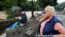 A woman looks at debris brought by the flood next to the Ahr river, following heavy rainfalls in Schuld, Germany, July 15, 2021. REUTERS/Wolfgang Rattay