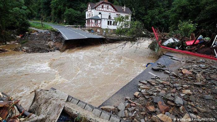 Raging river runs by a house on its bank with a partially destroyed road