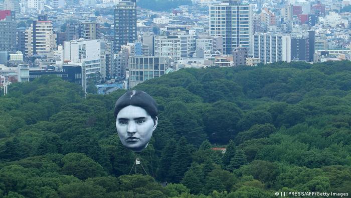 Balon sa ljudskim licem, juče iznad Jojogi parka u Tokiju, deo je umetničkog projekta grupe mé nazvanog Masajume - što znači san koji je postao stvarnost. Povodm Olimpijade ta grupa pušta ogromne balone sa licima ljudi iz svih krajeva sveta - ljudi koji postoje.