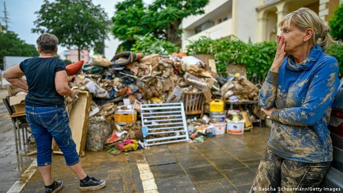 A flood victim standing next to the flood debris