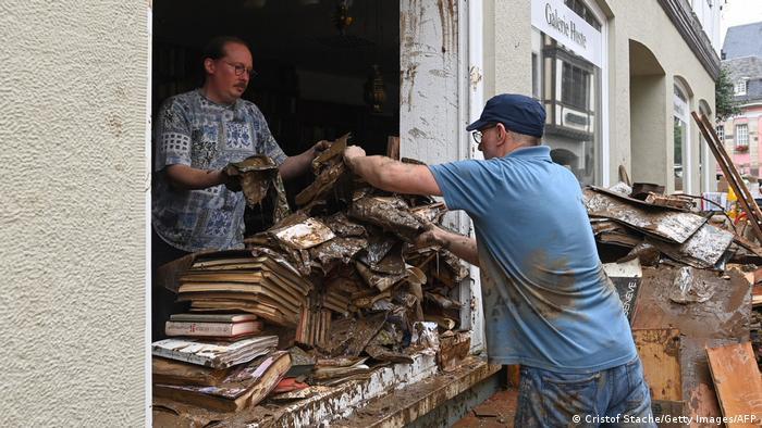 Two men in muddied shirts cleaning debris off a street in Bad Neuenahr-Ahrweiler