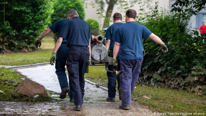 A team of four THW members carrying a motor pump