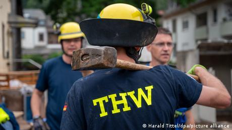 A THW crew member carrying a sledgehammer