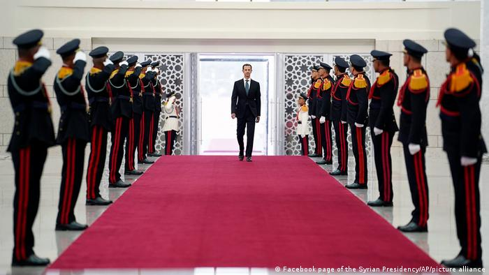 President Bashar Assad walks past soldiers at the Presidential Palace in Damascus, Syria