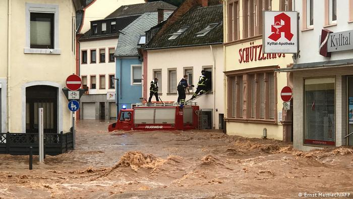 Firefighters standing on the roof of their truck to enter a flooded home in Trier, Germany, as floodwaters rush past