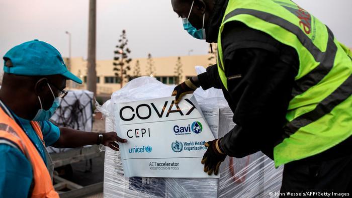 Covax-Impdosen werden von zwei Mitarbeitern am Flughafen von Dakar auf Paletten gestapelt.