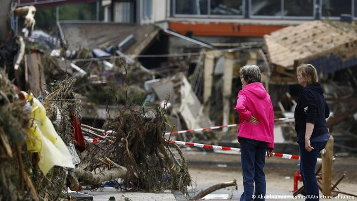 Two people look at debris in the wake of floods in Rhineland-Palatinate, Germany in July 2021